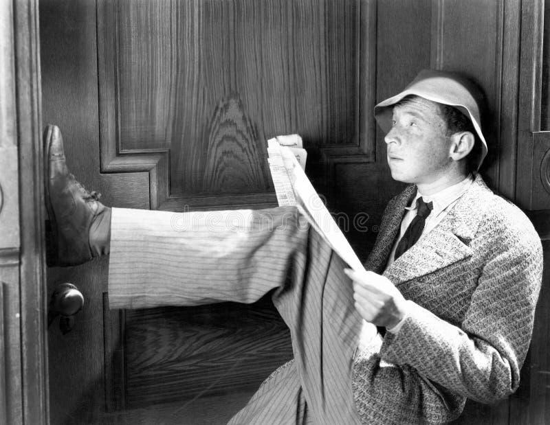 Mann, der an einer Tür mit seinen Beinen oben sich lehnt und eine Zeitung liest (alle ex Personen dargestellt sind nicht längeres lizenzfreie stockbilder