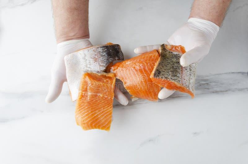 Mann, der einige Stücke frische rohe Lachse hält Geschmackvolle Stücke Fische lizenzfreie stockfotos