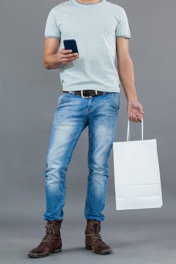 Mann, der Einkaufstasche hält und Handy verwendet lizenzfreies stockfoto
