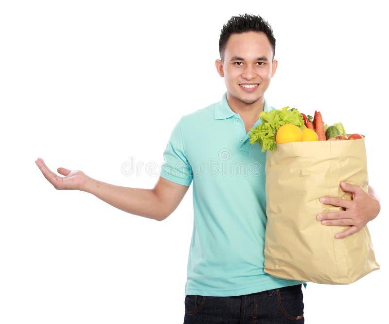 Mann, der Einkaufstasche voll vom Lebensmittelgeschäftdarstellen anhält lizenzfreies stockbild