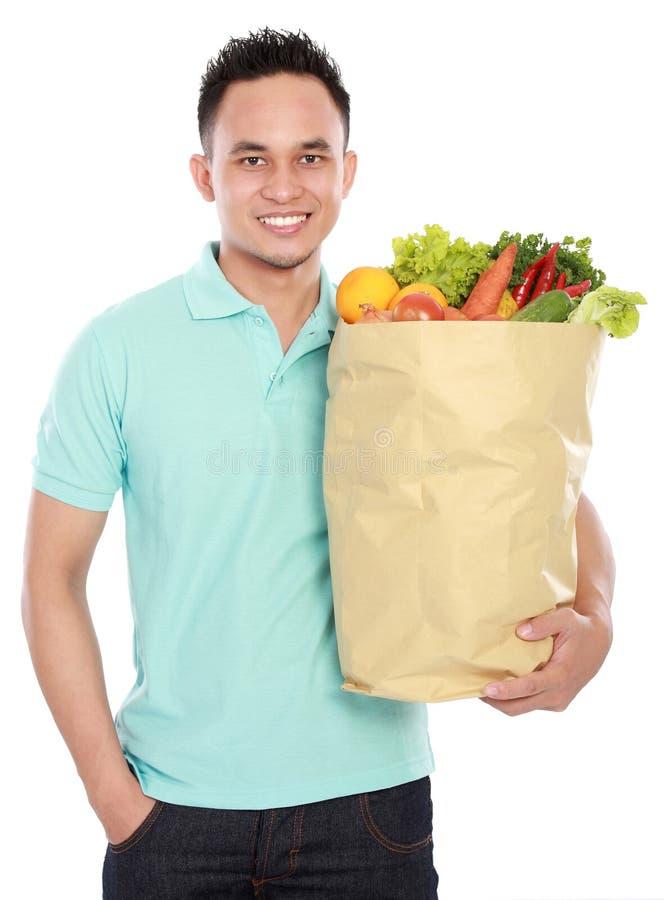 Mann, der Einkaufstasche voll von den Lebensmittelgeschäften anhält lizenzfreie stockbilder