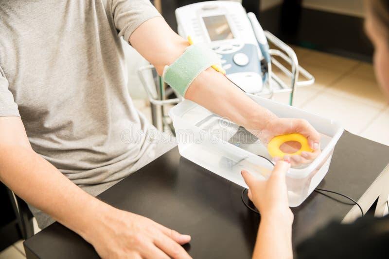 Mann, der Electrotherapy vom Physiotherapeuten In Hospital empfängt stockfoto
