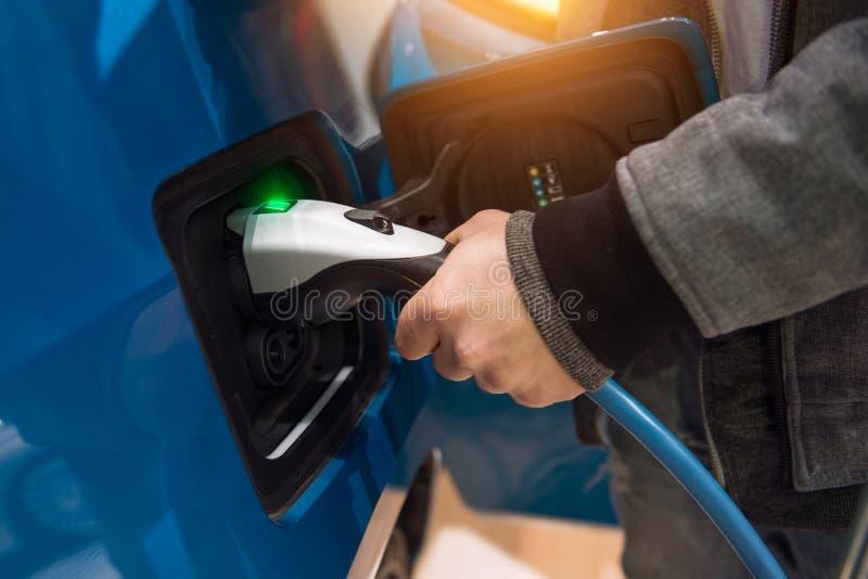 Mann, der Elektroauto an Ladestation auflädt Mann, der in der Hand Stromkabelversorgung angeschlossen hält lizenzfreie stockfotos