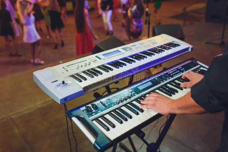 Mann, der elektronischen musikalischen Tastatursynthesizer durch H?nde auf den wei?en und schwarzen Schl?sseln im Tonstudio spiel lizenzfreie stockbilder