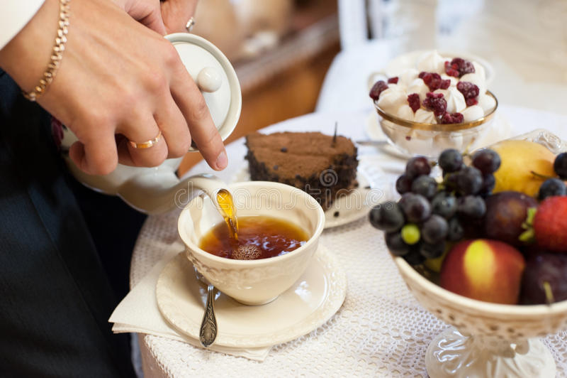 Mann, der englischen Tee in der Schale gießt stockfoto