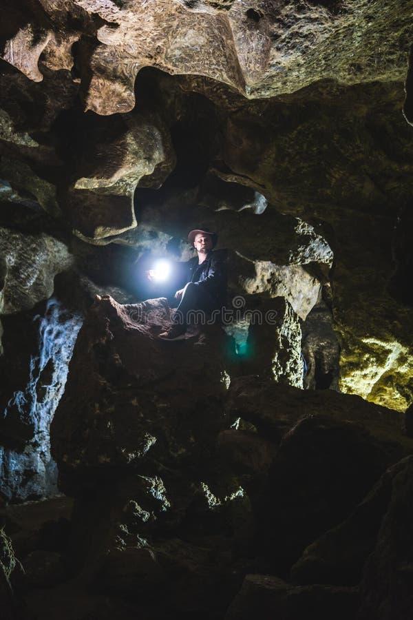 Mann, der enorme Höhle erforscht Abenteuerreisende kleideten Cowboyhut und Lederjacke extremer, touristischer Weg alter Kristall stockbild
