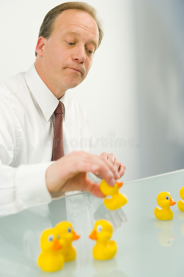 Mann, der Enten in eine Reihe einsetzt lizenzfreies stockbild