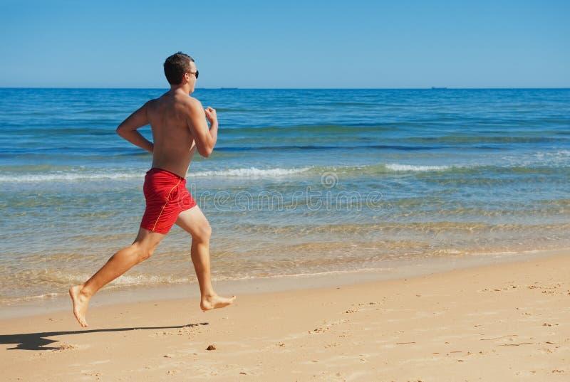 Mann, der entlang die Küste läuft stockfoto