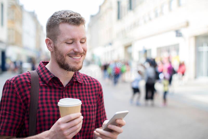 Mann, der entlang Stadt-Straßen-Lesetextnachricht auf beweglichem Pho geht stockbilder