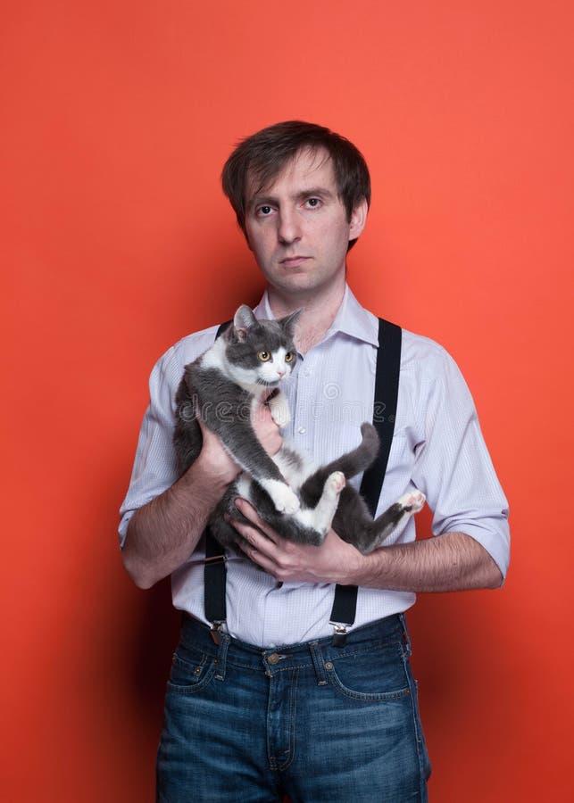 Mann, der entzückende graue Katze mit den weißen Tatzen auf orange Hintergrund hält lizenzfreie stockfotografie