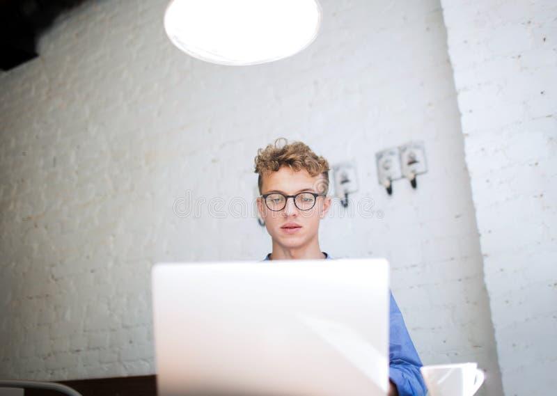 Mann in der erfolgreichen Entwicklung der Gläser von digitalen Projekten unter Verwendung des tragbaren Netzbuches lizenzfreie stockfotografie