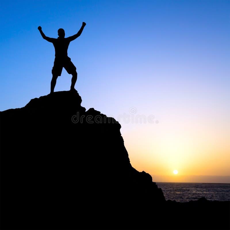 Mann, der Erfolgsschattenbild in den Bergen wandert stockfoto