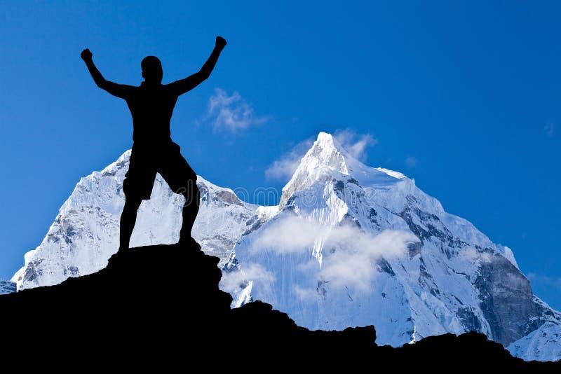 Mann, der Erfolgsschattenbild in den Bergen wandert lizenzfreie stockfotos