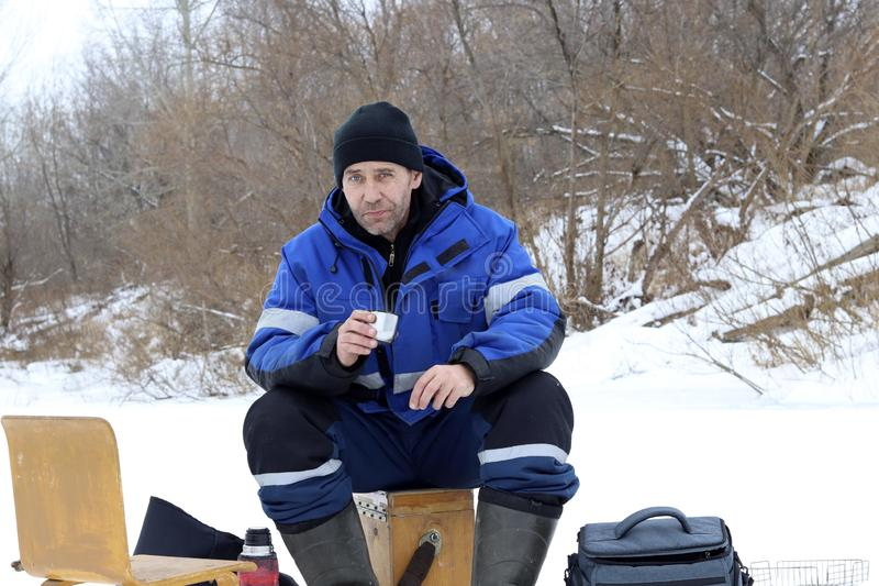 Mann, der Erwärmungsgetränk des Winters fischt stockfotografie