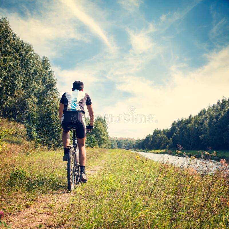 Mann, der Fahrrad auf Natur-Hintergrund fährt stockbild