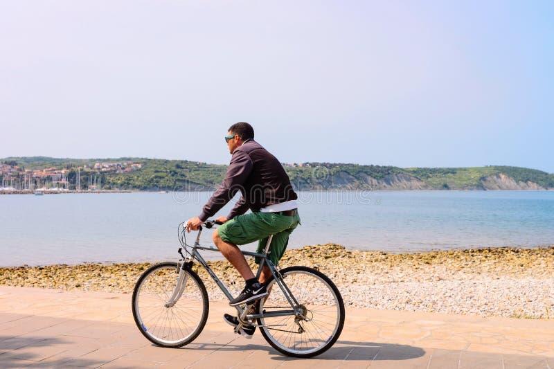 Mann, der Fahrrad am Damm des adriatischen Meeres in Izola-Fischerdorf, Slowenien fährt lizenzfreies stockbild