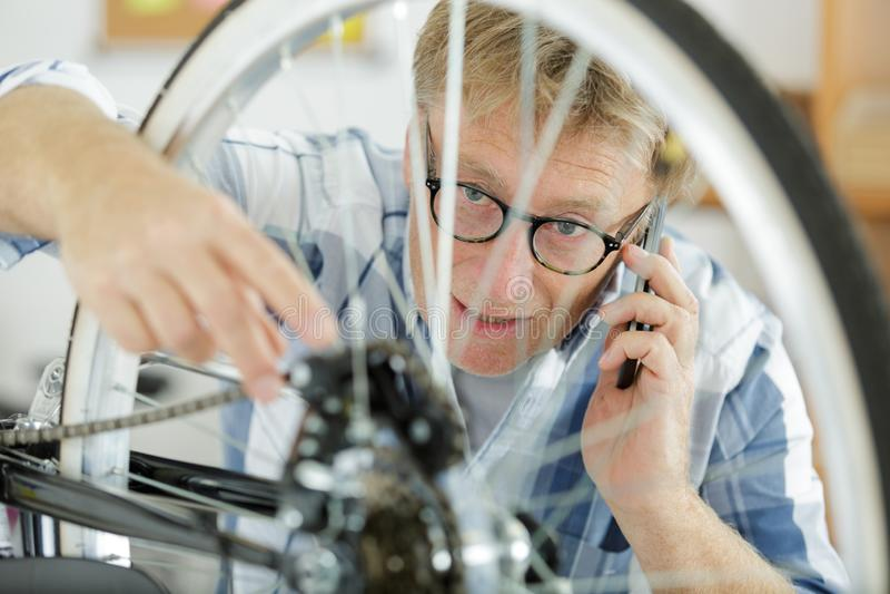 Mann, der an Fahrradreifen beim Ersuchen um Telefon arbeitet stockfoto