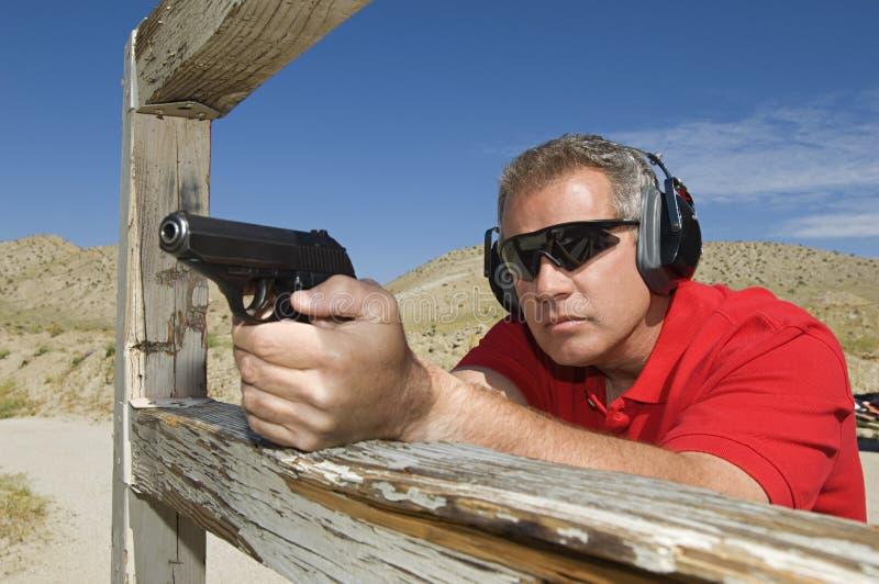 Mann, der Faustfeuerwaffe auf Schießstand abzielt stockfoto