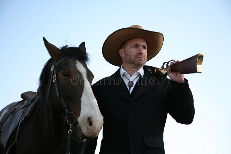 Mann in der feinen alten westlichen Kleidung mit Pferd u. Gewehr lizenzfreies stockfoto