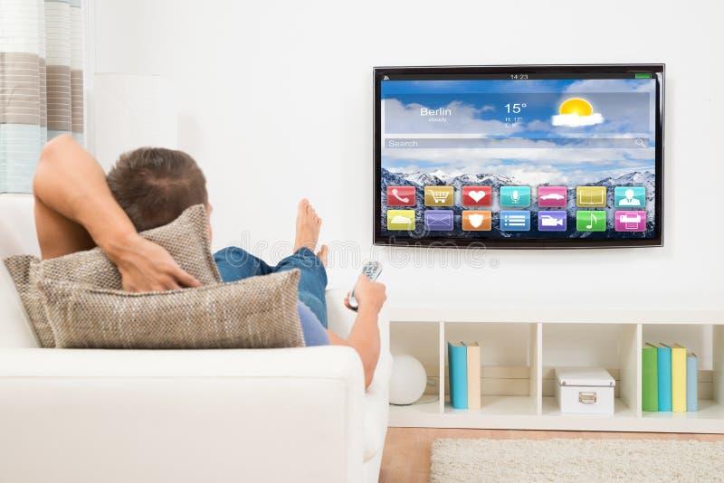 Mann, der Fernbedienung in Front Of Television verwendet stockbild