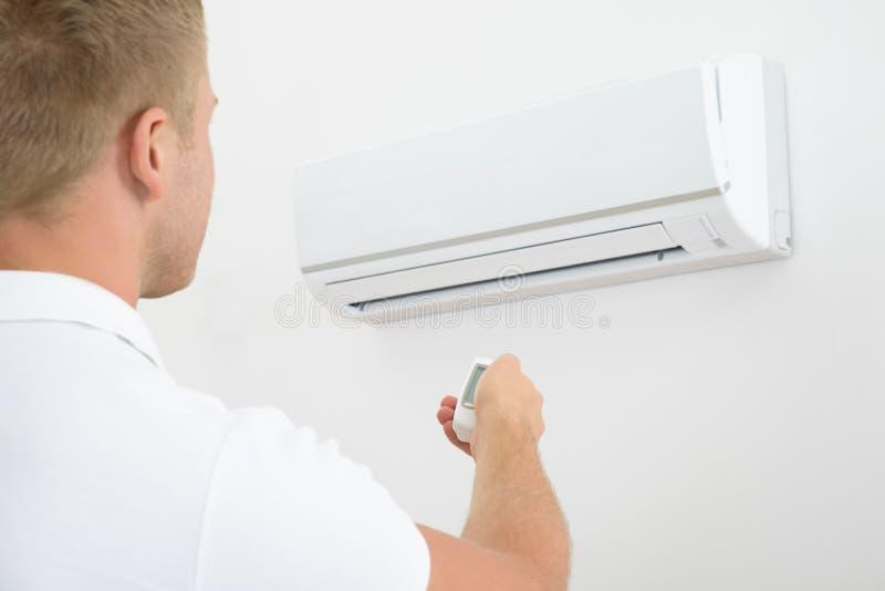 Mann, der Fernprüfer der Klimaanlage hält stockbild