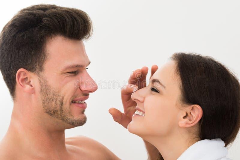 Mann, der Feuchtigkeitscreme auf der Nase der Frau anwendet stockbilder