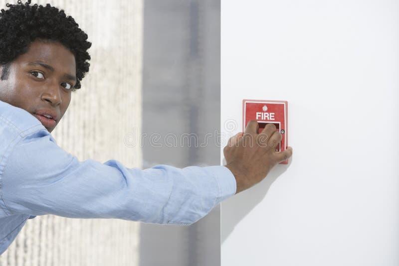 Mann, der Feuermelder anstellt stockbilder