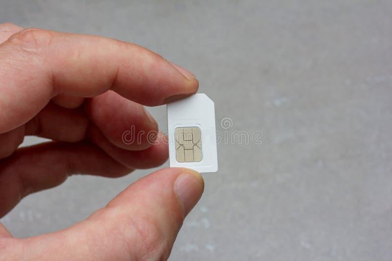 Mann, der Finger SIM-Karte auf grauem Hintergrund hält lizenzfreie stockfotografie
