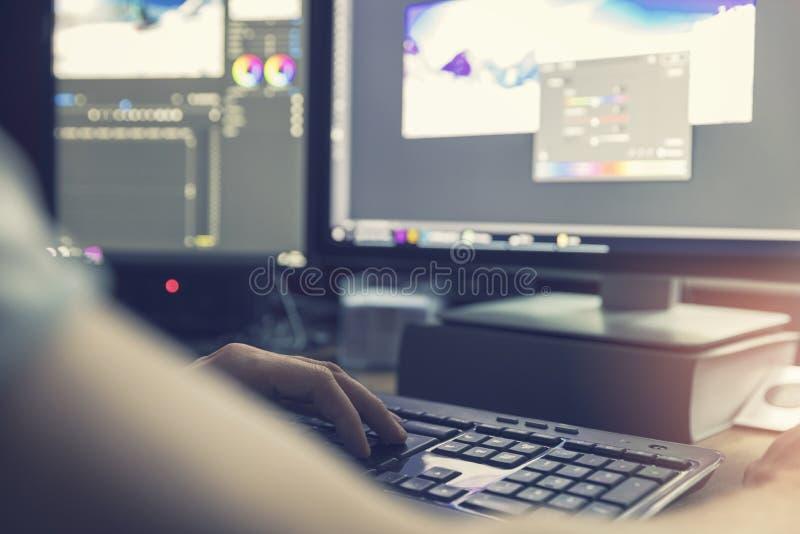 Mann, der Foto und Videobearbeitung auf Computer tut stockbild