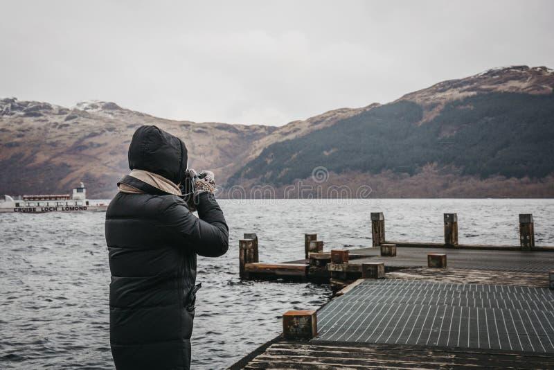 Mann, der Fotos auf einem Pier auf Loch Lomond in Schottland macht stockfotografie