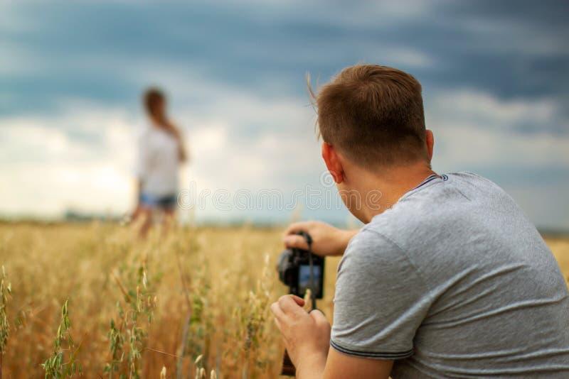 Mann, der Fotos seiner Freundin im Freien macht Paarfreizeit und -zeitvertreib lizenzfreies stockbild