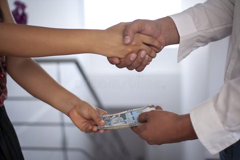 Mann, der der Frau peruanisches Geld beim Rütteln von Händen zahlt lizenzfreie stockfotos