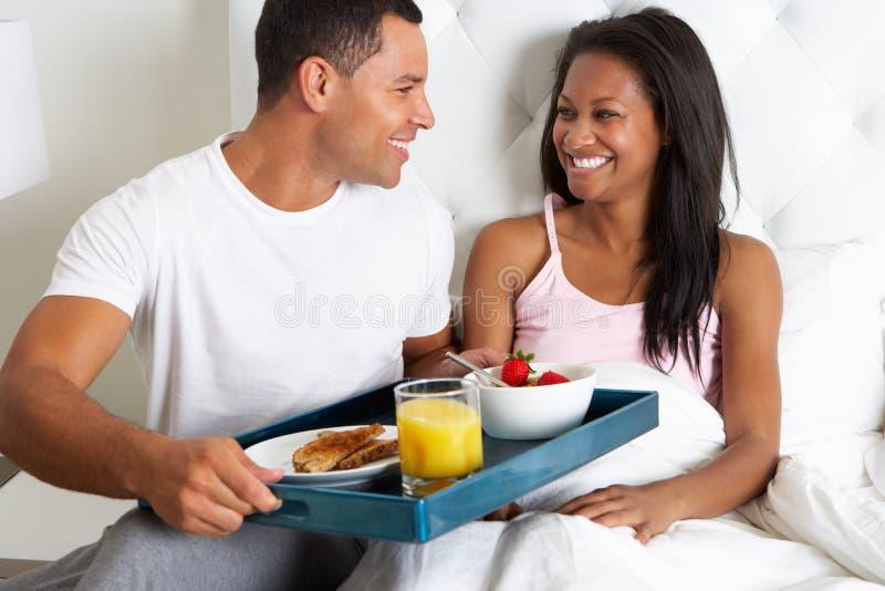 Mann, der Frauen-Frühstück im Bett auf Behälter holt stockfotografie