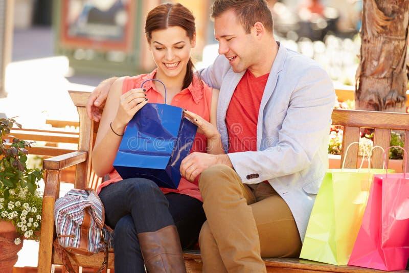 Mann, der Frauen-Geschenk als sie Sit On Seat In Shopping-Mall gibt stockbild