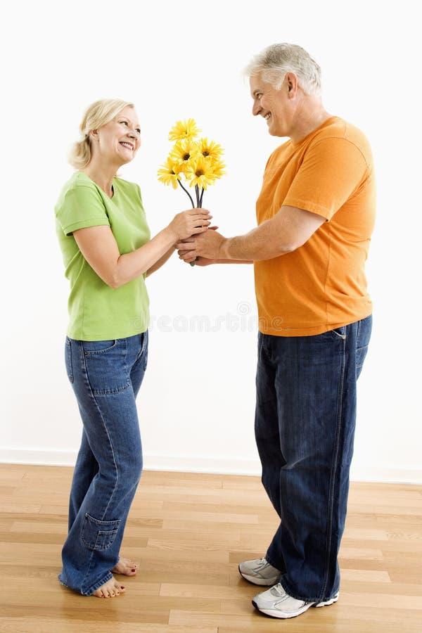 Mann, der Frauenblumenstrauß gibt. lizenzfreie stockfotos