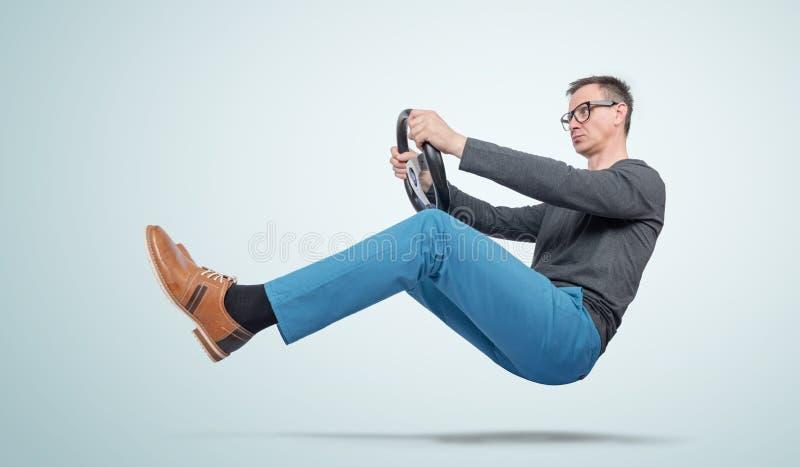 Mann in der Freizeitkleidung und in den Gläsern fährt ein Auto mit einem Lenkrad Selbstfahrerkonzept stockbild