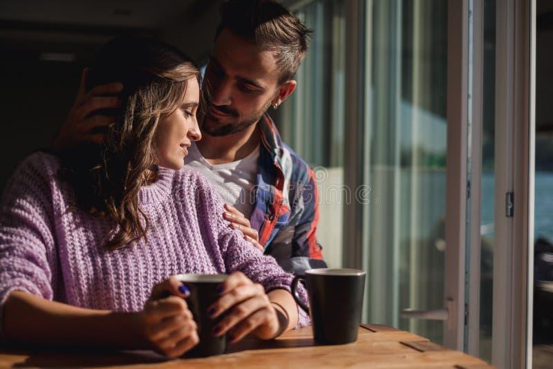 Mann, der Freundin umarmt, während sie Kaffee am Fenster trinken lizenzfreie stockbilder