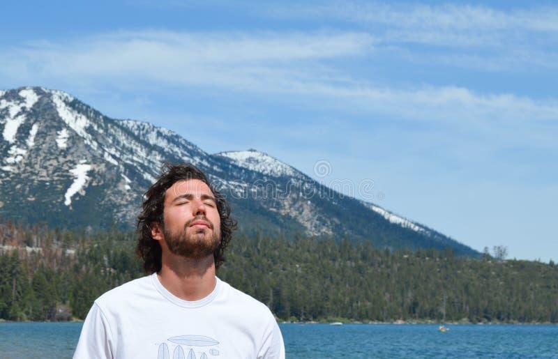 Mann, der Frieden in Lake Tahoe, Kalifornien einatmt Schneeberge auf dem Hintergrund lizenzfreie stockfotografie