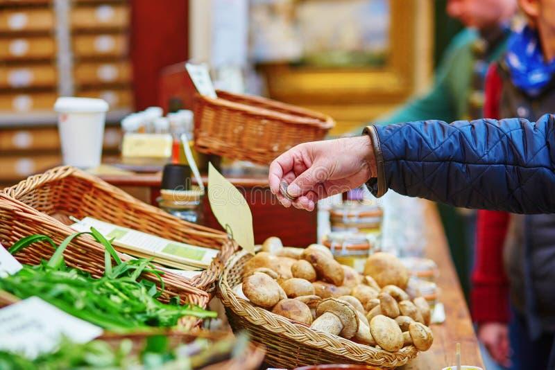 Mann, der frische Pilze auf Markt kauft lizenzfreie stockfotografie