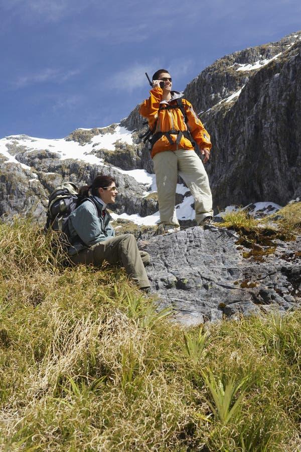 Mann, der Funksprechgerät als Frauen-Reste auf Felsen verwendet lizenzfreie stockbilder