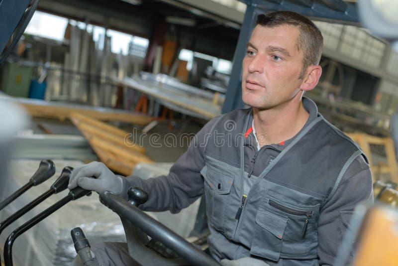 Mann, der Gabelstapler innerhalb des Lagers fährt stockfotografie