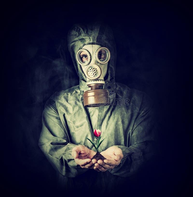 Mann in der Gasmaske, die Blume in den Palmen hält lizenzfreie stockfotos