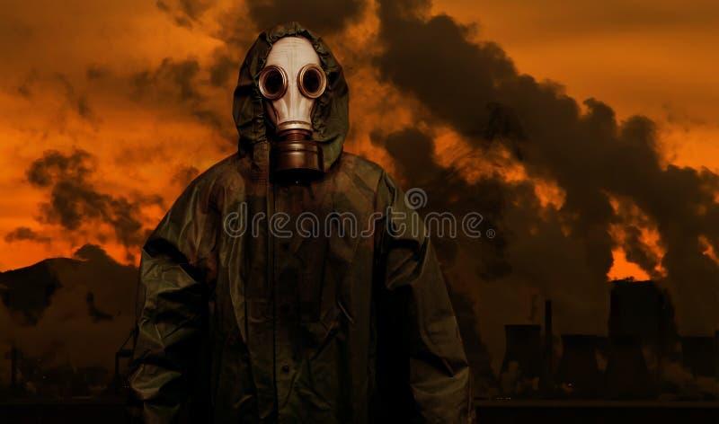 Mann in der Gasmaske und im Mantel des Chemikalienschutzes mit Schwerindustrieanlagen lizenzfreies stockfoto