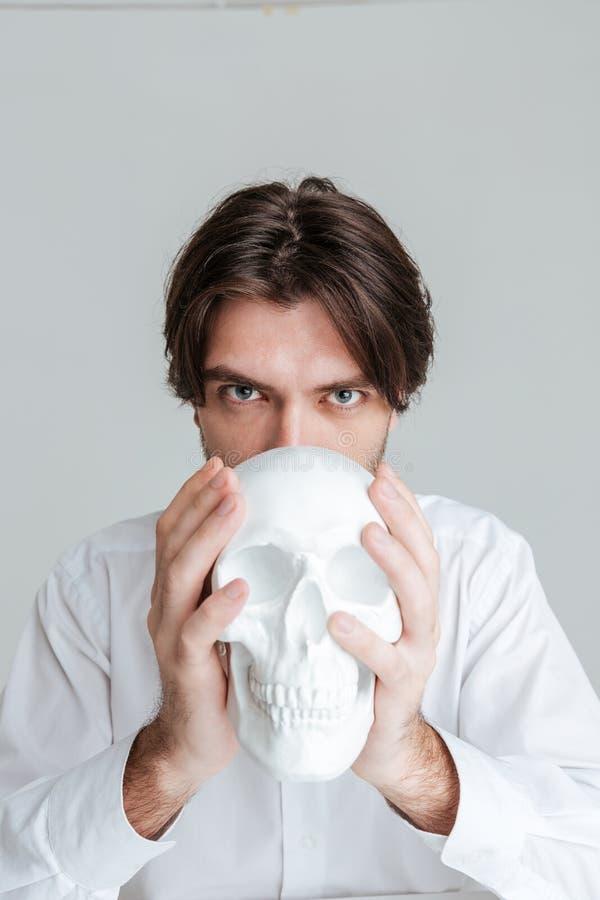 Mann, der gefälschten Schädel an seinem Gesicht hält lizenzfreies stockfoto