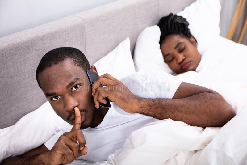 Mann, der geheim auf Mobiltelefon w?hrend sein Frau-Schlafen spricht lizenzfreies stockbild