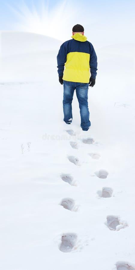 Mann in der gelben Jacke gehend auf Schnee lizenzfreie stockfotos
