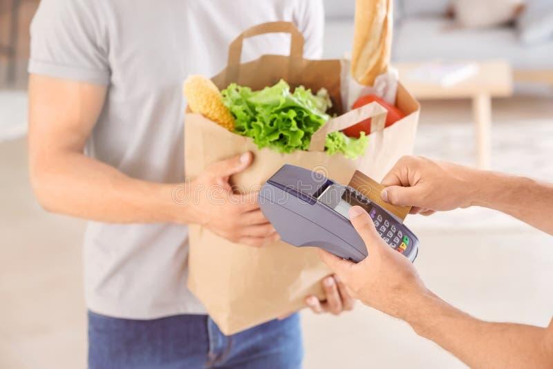 Mann, der Geld für Nahrungsmittellieferung von der Kreditkarte des Kunden unter Verwendung des Bankanschlusses entfernt stockbild