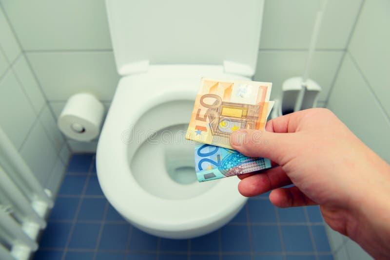 Mann, der Geld in der Toilette wegwirft stockfotos