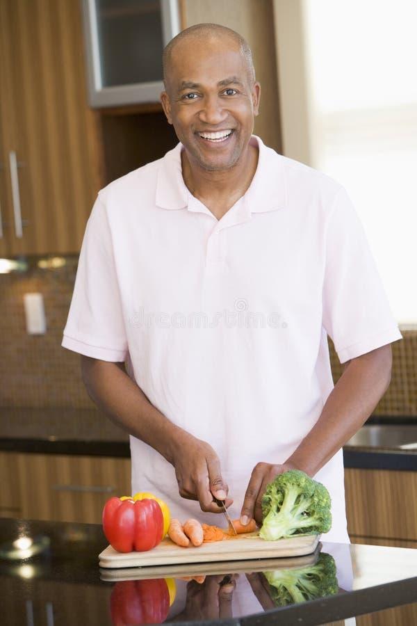 Mann, der Gemüse hackt stockbilder