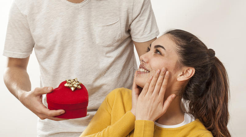 Mann, der Geschenkbox hält und Freundin gibt stockfotografie